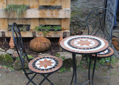 Vor dem Eingang Tisch mit zwei Stühlen